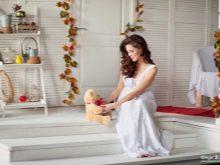Беременная с мягкой игрушкой в фотостудии