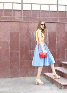 Яркая сумочка в дополнение к голубой юбке