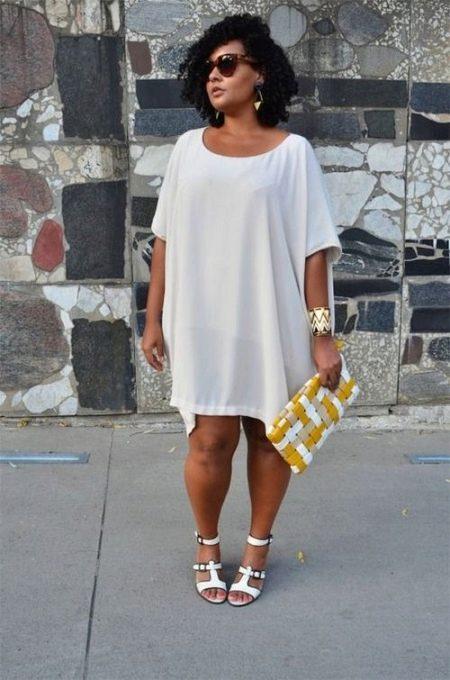 Белое платье-туника для полных женщин в сочетание с белыми босоножками и золотыми аксессуарами